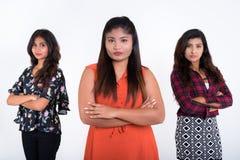 Trois jeunes amies persanes de femme avec des bras ont croisé ensemble l'aga Photos stock