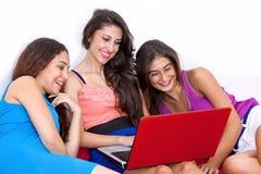 Trois jeunes amies s'asseyant et se trouvant sur le sofa avec l'ordinateur portable. Photos libres de droits
