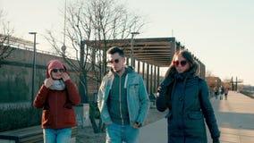 Trois jeunes amis adultes sont parlants et marchants sur Quay moderne en Sunny Day banque de vidéos