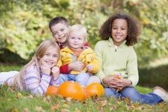 Trois jeunes amis avec la chéri et les potirons Image libre de droits