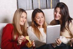Trois jeunes amis ayant l'amusement et à l'aide du comprimé Photographie stock libre de droits