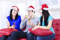 Trois jeunes amis buvant du champagne Photographie stock