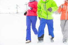 Trois jeunes amis courant dans la neige Images libres de droits