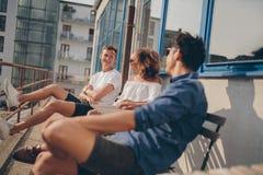 Trois jeunes amis détendant au café extérieur Photographie stock