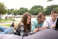 Trois jeunes amis détendant dehors en parc sur un grand cushi Images stock