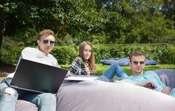 Trois jeunes amis d'étudiant détendant dehors sur un grand coussin, Image stock