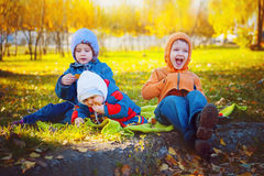 Trois jeunes amis de sourire s'asseyant sur l'herbe Image stock