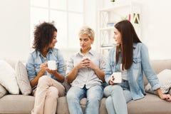 Trois jeunes amis féminins avec du café causant à la maison Image stock