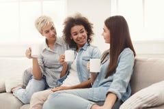 Trois jeunes amis féminins avec du café causant à la maison Photographie stock libre de droits