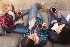 Trois jeunes amis féminins avec du café causant à la maison Image libre de droits