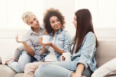 Trois jeunes amis féminins avec du café conversant Photographie stock