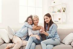 Trois jeunes amis féminins causant à la maison Photographie stock
