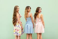 Trois jeunes amis féminins dans des robes mignonnes ont retourné l'épaule Photos stock