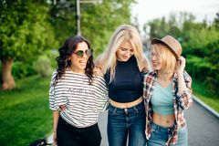 Trois jeunes amis féminins marchant sur le parc jeunes femmes flânant le jour d'été Photo stock