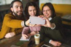 Trois jeunes amis heureux prenant le selfie avec le smartphone en café Photographie stock
