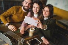 Trois jeunes amis heureux prenant le selfie avec le smartphone en café Image stock