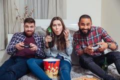 Trois jeunes amis jouant des jeux d'ordinateur et buvant de la bière Images libres de droits