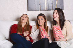 Trois jeunes amis mangeant du maïs éclaté et observant des films Image stock