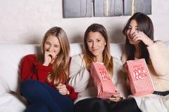 Trois jeunes amis mangeant du maïs éclaté et observant des films Photographie stock