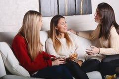 Trois jeunes amis parlant et mangeant Photos stock