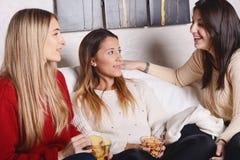 Trois jeunes amis parlant et mangeant Photographie stock libre de droits