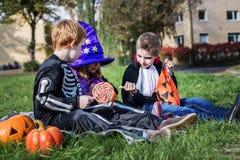 Trois jeunes amis partageant des sucreries de Halloween Photo stock