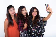 Trois jeunes amis persans heureux de femme souriant tout en prenant le sel Photo stock
