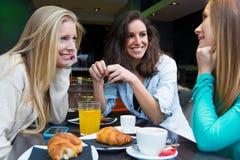 Trois jeunes amis prenant le petit déjeuner sur des achats de matin en Th Photographie stock libre de droits