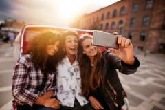 Trois jeunes amis prenant le selfie sur le tour de tricycle Photographie stock