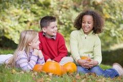 Trois jeunes amis s'asseyant sur l'herbe avec des potirons Image stock