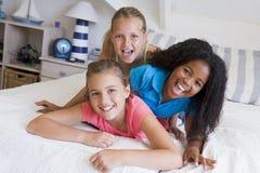 Trois jeunes amis se trouvant sur l'un l'autre Image libre de droits