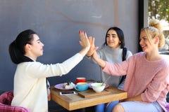Trois jeunes belles amies de filles vibrent, se réjouissent, la haute cinq Image stock
