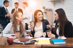 Trois jeunes belles filles socialisent le café potable et la consommation durcit dans le bureau Photographie stock libre de droits