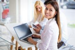 Trois jeunes collègues de sourire travaillant ensemble sur l'ordinateur portable image stock