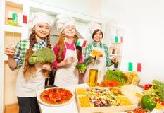 Trois jeunes cuisiniers d'Italien à la cuisine photo libre de droits