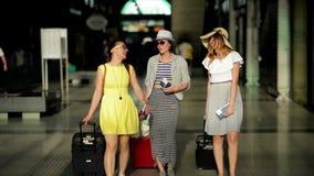 Trois jeunes dames mignonnes portant des robes d'été ont un voyage ensemble Brunes étonnantes avec Laggage à l'aéroport banque de vidéos