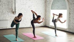 Trois jeunes dames pratiquent le seigneur de la pose Natarajasana de danse tout en faisant le yoga au centre moderne de bien-être banque de vidéos