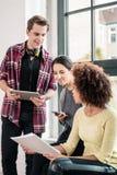 Trois jeunes employés à l'aide des dispositifs modernes pendant la coupure photos stock