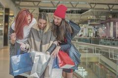 Trois jeunes et jolies filles tiennent les paniers et le g images stock