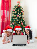 Trois jeunes femmes à l'aide d'un ordinateur portable devant l'arbre de Noël Image stock