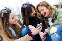Trois jeunes femmes à l'aide d'un téléphone portable dans la rue Photo libre de droits