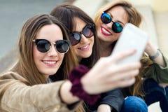 Trois jeunes femmes à l'aide d'un téléphone portable dans la rue Images libres de droits
