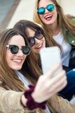 Trois jeunes femmes à l'aide d'un téléphone portable dans la rue Photos stock