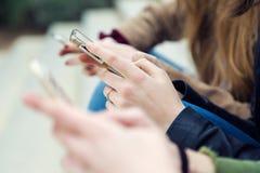 Trois jeunes femmes à l'aide d'un téléphone portable dans la rue Photos libres de droits