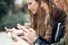 Trois jeunes femmes à l'aide d'un téléphone portable dans la rue Image stock