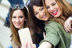 Trois jeunes femmes à l'aide d'un téléphone portable dans la rue Image libre de droits