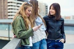 Trois jeunes femmes à l'aide d'un téléphone portable dans la rue Photographie stock libre de droits