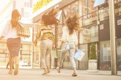 Trois jeunes femmes à la mode flânant avec des paniers Image stock