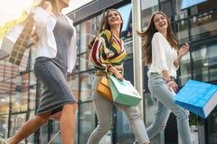 Trois jeunes femmes à la mode flânant avec des paniers Photos stock