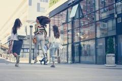 Trois jeunes femmes à la mode flânant avec des paniers de Photo libre de droits
